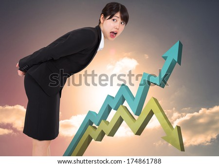 Surprised businesswoman bending against blue and green arrows against blue sky - stock photo