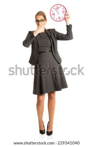 Surprised businesswoman holding a big clock. - stock photo