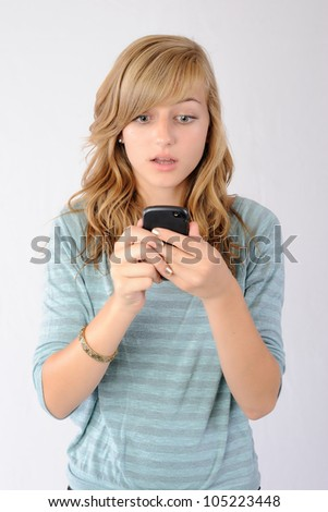 Surprised by Text Message. Thirteen year old girl reacting to a text message with shock and disbelief. Note: Not Isolated. - stock photo