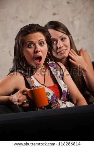 Surprised Caucasian woman with friend whispering in her ear - stock photo