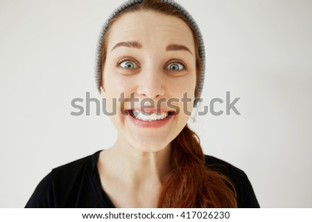 Surprised Caucasian woman with red hair and blue eyes looking and smiling at the camera in astonishment and shock. Funny hipster girl having fun posing with happy expression against studio wall.  - stock photo