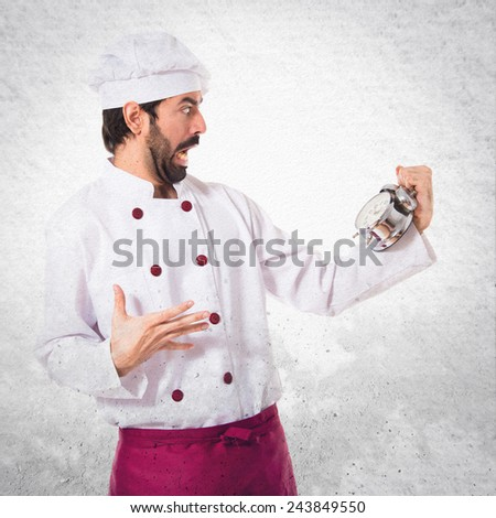 Surprised chef holding a clock over textured background - stock photo