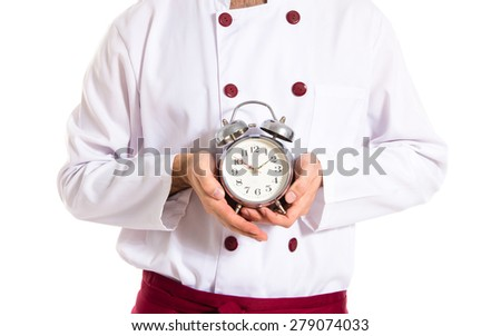 Surprised chef holding a clock over white background