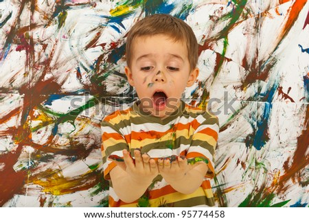 Surprised child boy looking at his messy palms  against painted background