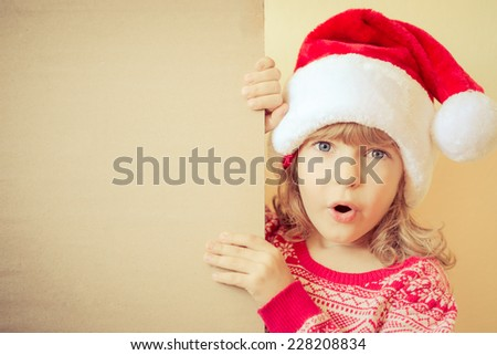 Surprised child holding Christmas card blank. Funny kid dressed in Santa Claus hat playing at home. Xmas holiday concept. Copy space for your text