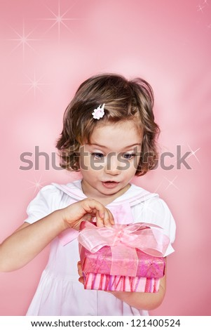 Surprised child opening pink present - stock photo