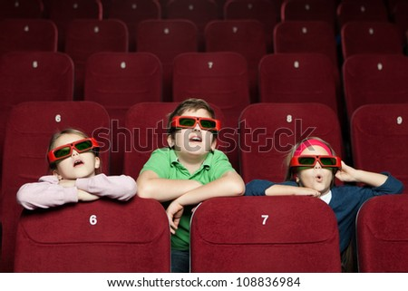 Surprised children watching a movie  at the 3D cinema - stock photo