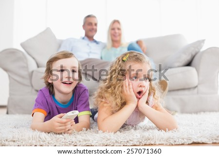 Surprised children watching TV while parents sitting on sofa at home - stock photo