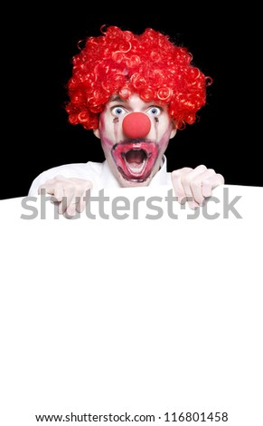 Surprised Clown In Facepaint Holding Blank Copyspace Sign Board On Black Studio Background - stock photo