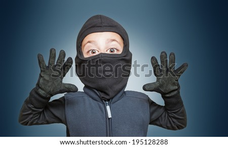 Surprised comic burglar stopped and take his hands up - stock photo