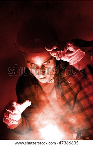 Surprised constructor worker looking at a light in a dark background