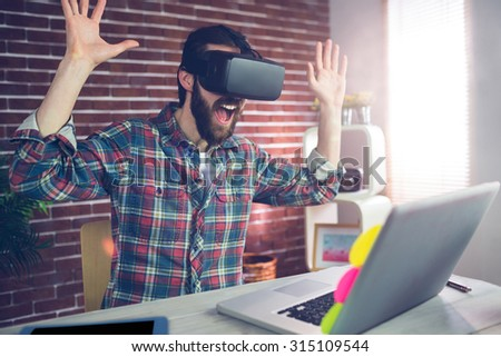 Surprised creative businessman wearing 3D video glasses while working in office - stock photo
