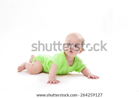 Surprised cute baby lying on his stomach and looking at the camera, picture with depth of field