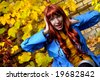 Surprised emotional girl against autumn leaves - stock photo