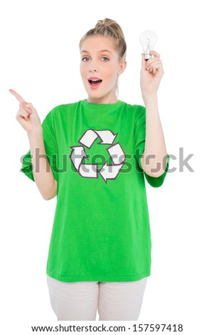 Surprised environmental activist wearing recycling tshirt holding light bulb on white background - stock photo