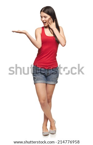 Surprised excited woman. Full length of beautiful woman showing holding  blank copy space on the palm, looking at palm, over white background - stock photo