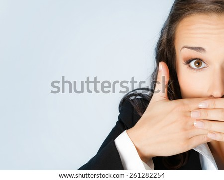 Surprised excited young businesswoman covering with hands her mouth, against blue background - stock photo