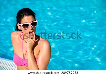 Surprised expressive woman at swimming pool on summer vacation. Adult girl in bikini doing thinking gesture against blue clear water background. - stock photo