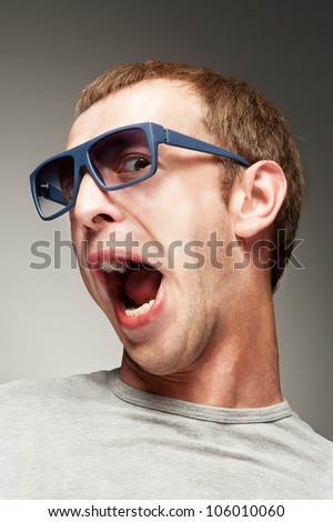 Surprised face expression. Young man in sun glasses with surprised smile/Surprised young man/surprised smile. Grey background. Studio shot. - stock photo