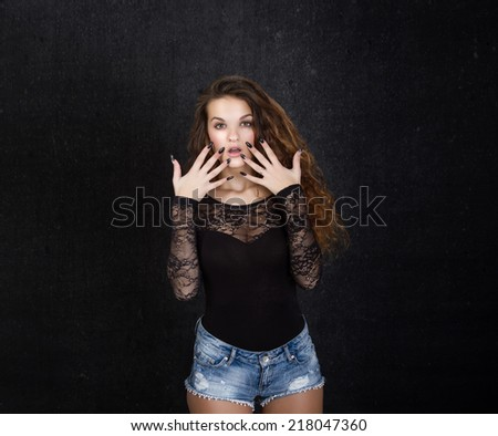 surprised face for girl on dark background - stock photo