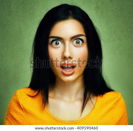 Surprised face of amazed shocked young woman - stock photo