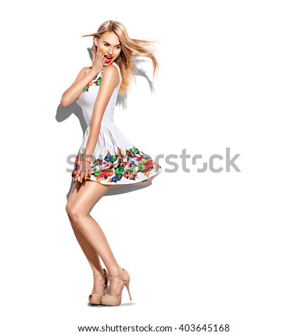 Surprised Fashion model Girl full length portrait dressed in short white dress and beige high-heeled shoes. Blowing blonde hair. Beautiful young woman posing in studio, emotions, looking back - stock photo