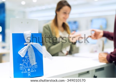 Surprised female getting present at shop. She is taking present with both hands. Blue bag with present is at selective focus, female is out of focus in background. Copy space. Shallow depth of field. - stock photo