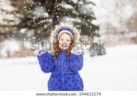 Surprised funny girl raised her hands in the air, catching snowflakes in winter park. - stock photo