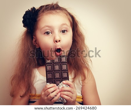 Surprised funny girl with open mouth and big eyes holding chocolate and looking. Vintage closeup portrait with empty copy space - stock photo