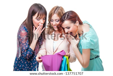 Surprised girl friends looking into shopping bag, isolated on white background