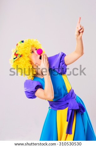 Surprised girl in a clown's costume pointing up