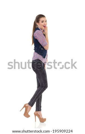 Surprised girl in jeans waistcoat walking. Happy girl in jeans waistcoat walking and looking at camera. Full length studio shot isolated on white.