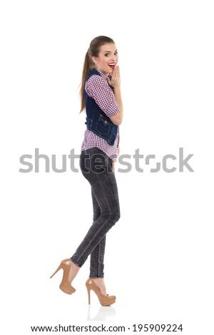 Surprised girl in jeans waistcoat walking. Happy girl in jeans waistcoat walking and looking at camera. Full length studio shot isolated on white. - stock photo