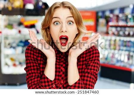 Surprised girl in the shop - stock photo