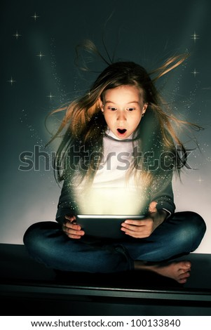 Surprised girl looking at a magic tablet. Child with tablet computer - stock photo