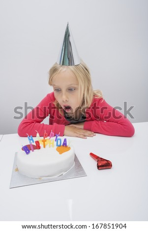Surprised girl looking at birthday cake on table in house - stock photo