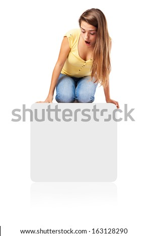 surprised girl looking down sitting on a paper poster - stock photo