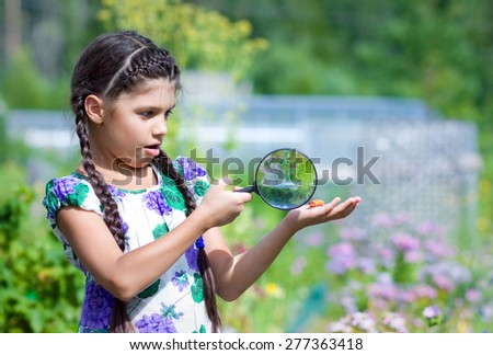 Surprised girl looking through magnifying glass on beetle - stock photo