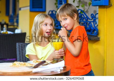Surprised girl looks at the boy drinking juice