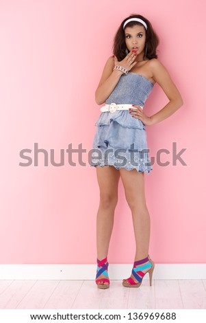 Surprised girl standing over pink wall, wearing mini dress.