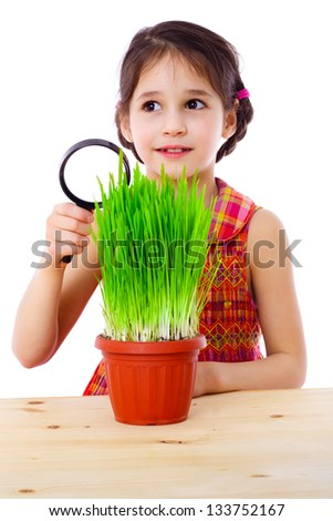 Surprised girl with magnifying glass and green grass on the table , isolated on white