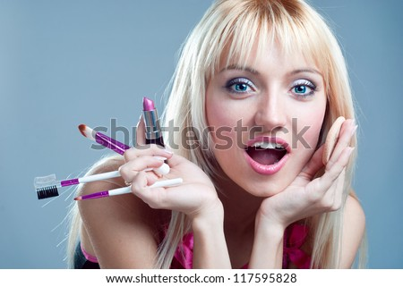 Surprised girl with makeup in the hands of - stock photo