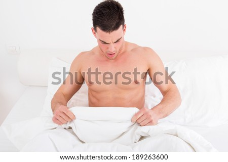 surprised half naked young man in bed  looking down at his underwear at his penis under white covers sheet in bedroom. Concept photo of male sexuality and man sex problems, domestic atmosphere. - stock photo