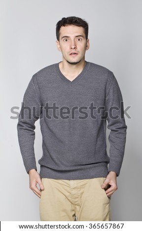 Surprised handsome man in grey sweater.