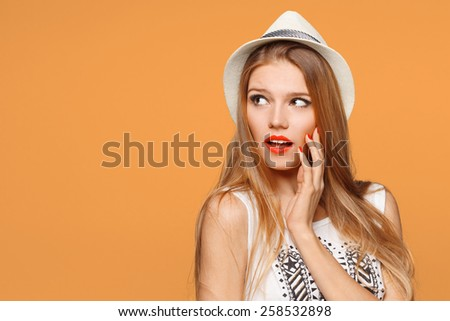 Surprised happy beautiful woman looking sideways in excitement. Isolated over orange background - stock photo