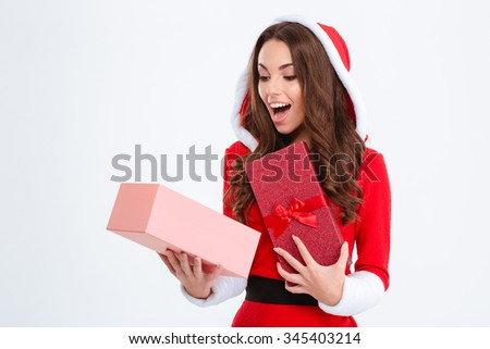 Surprised happy content curly young female in red santa claus costume with hood looking inside present box on white background - stock photo