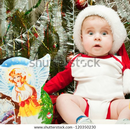 surprised kid in christmas suit with decorated fir tree - stock photo