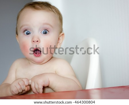 surprised kid sitting at table. child's eyes widened and mouth opened in amazement. copy space for your text