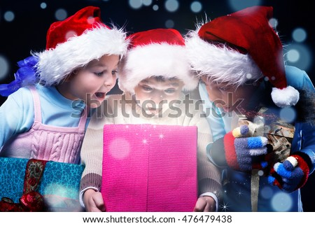 Surprised kids scream at opening a present box magic light inside