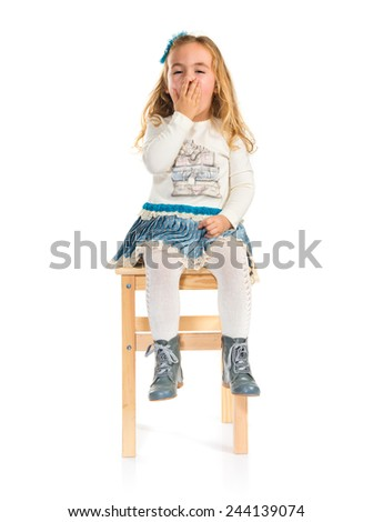 Surprised little blonde girl sitting on chair - stock photo